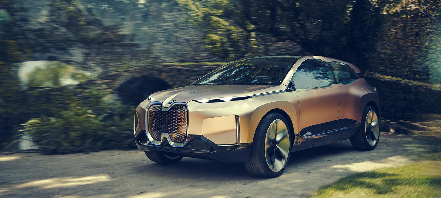 Three quarter front shot of the BMW Vision iNEXT in front of stone wall