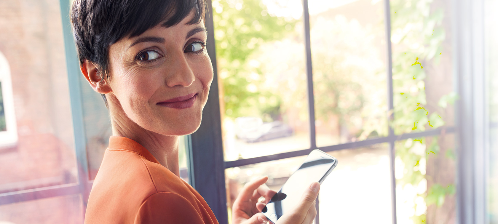 Dark-haired woman in orange jacket in front of window looking at her smartphone