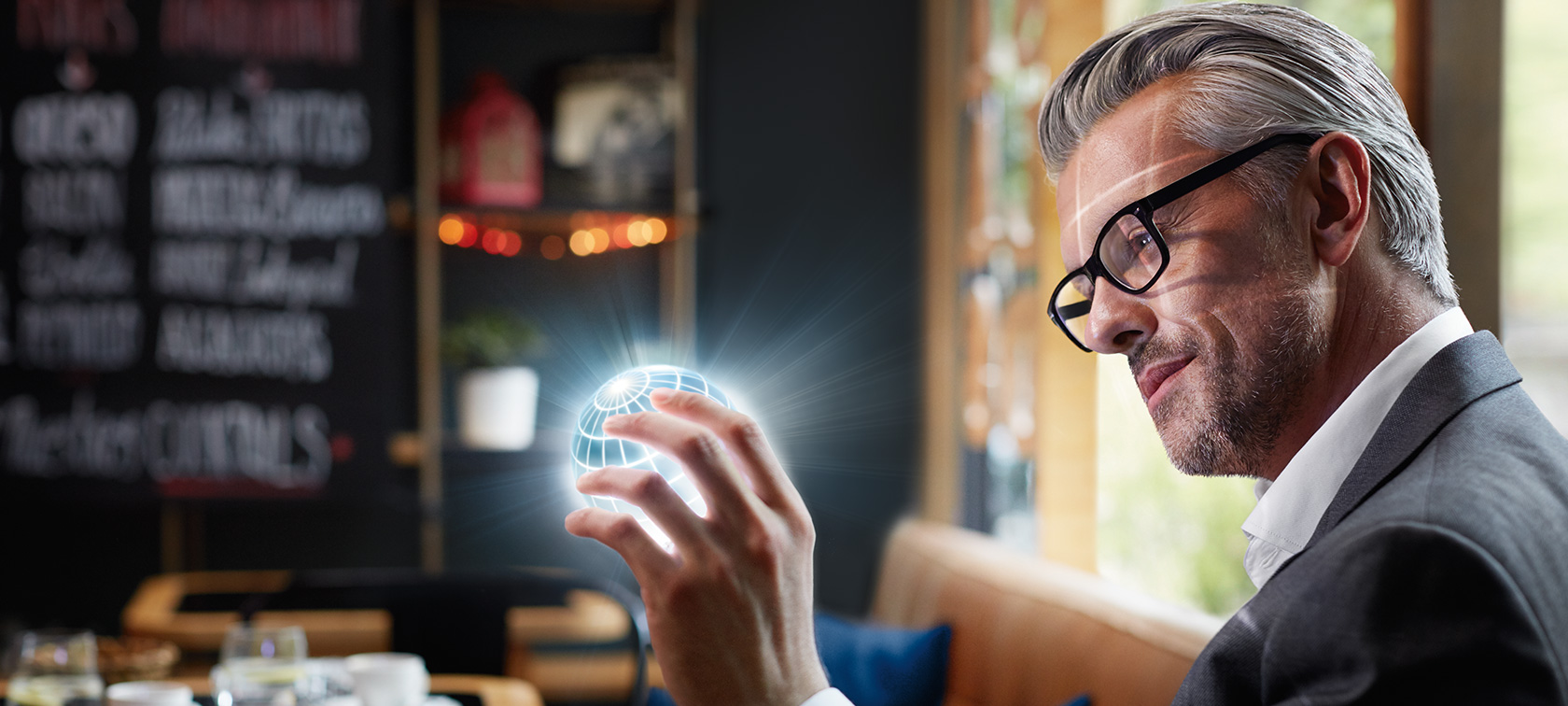 Man holds ConnectedDrive globe in his hands and is fascinated.